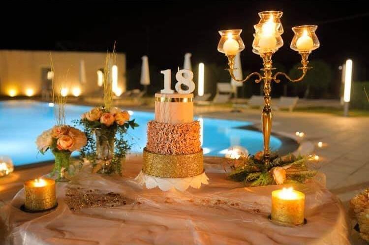 tavolo con piscina alle spalle con torta 18esimo compleanno